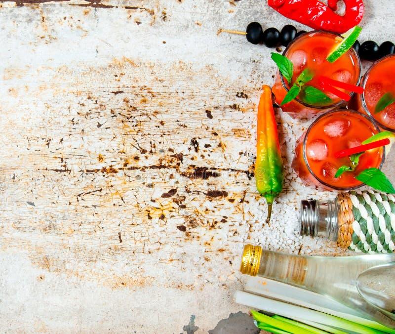 Koktajl robić pomidory, ajerówka, lód, wapno, pieprz, sól i przekąska z oliwkami, selerowymi i czarnymi na nieociosanym tle zdjęcie royalty free