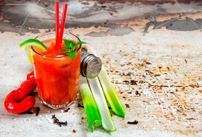Koktajl robić pomidory, ajerówka, lód, wapno, pieprz, sól i przekąska z selerem, na nieociosanym tle Uwalnia przestrzeń dla tekst fotografia stock