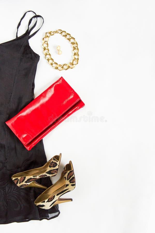 Koktajl sukni strój, noc out patrzeje na białym tle Mała czerni suknia, czerwieni sprzęgło, lampartów buty, złocista kolia i earr zdjęcia stock