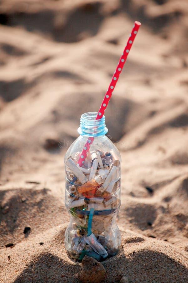 Koktajl z śmieci i słomą na czystej plaży Plastikowy oceanu zanieczyszczenie, środowiskowy kryzys Mówić nie klingeryt U?ywa kling obraz royalty free
