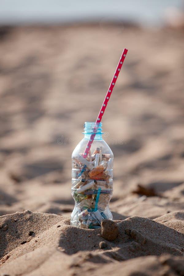 Koktajl z śmieci i słomą na czystej plaży Plastikowy oceanu zanieczyszczenie, środowiskowy kryzys Mówić nie klingeryt U?ywa kling zdjęcie stock