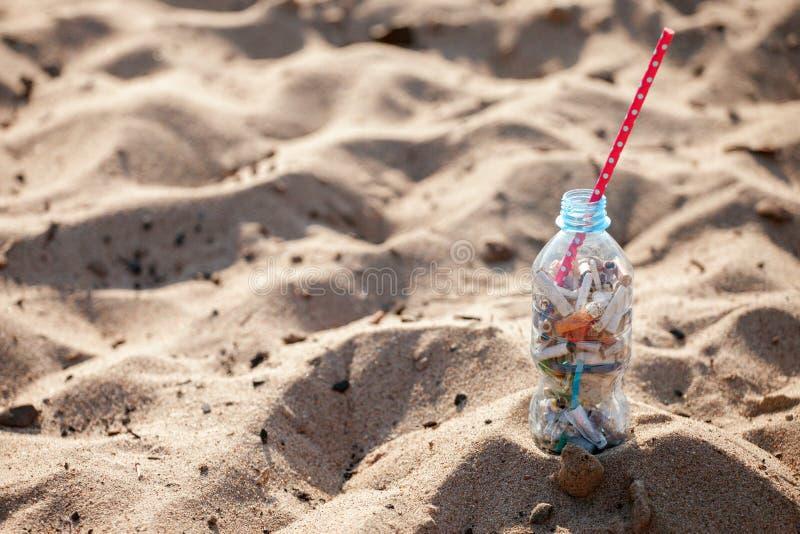 Koktajl z śmieci i słomą na czystej plaży Plastikowy oceanu zanieczyszczenie, środowiskowy kryzys Mówić nie klingeryt U?ywa kling zdjęcie royalty free