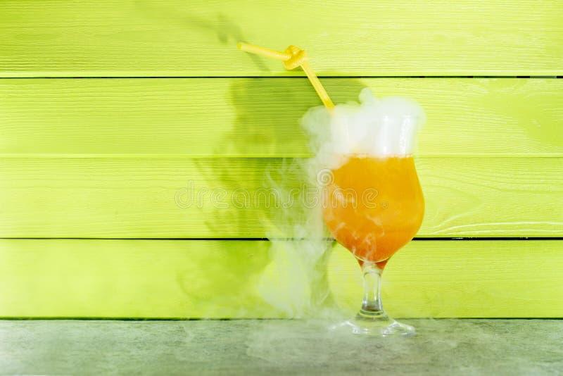 Koktajl z ciekłym azotem Lato chłodniczy pomarańczowy koktajl w szklanej zlewce z słomą ciek?y azot obrazy royalty free