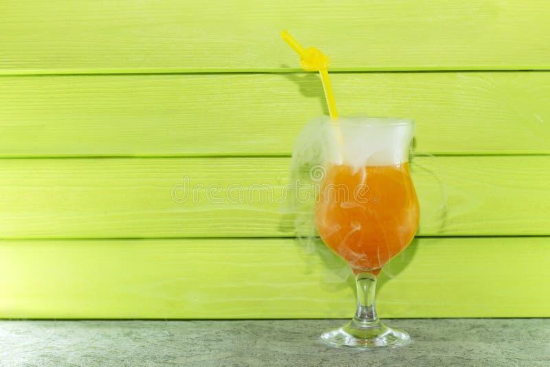 Koktajl z ciekłym azotem Lato chłodniczy pomarańczowy koktajl w szklanej zlewce z słomą ciek?y azot zdjęcie royalty free