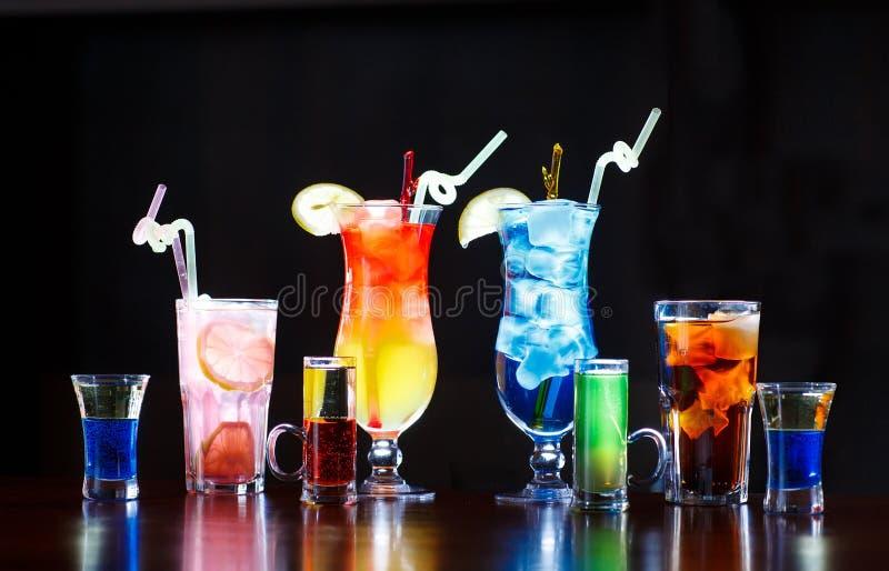 Koktajle na barze odpierającym na czarnym tle zdjęcia stock