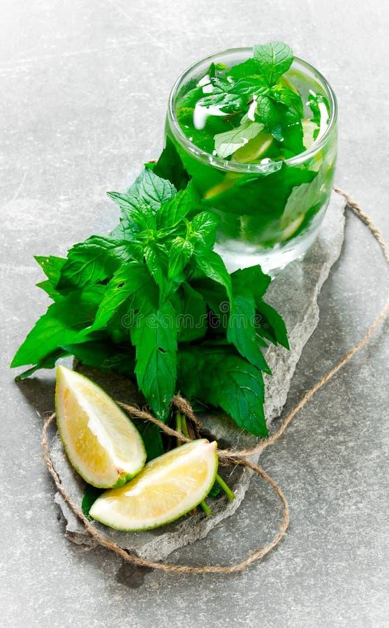 Koktajlu szkło - wybija monety, zamraża, rum i wapno na kamiennym piedestale zdjęcie stock