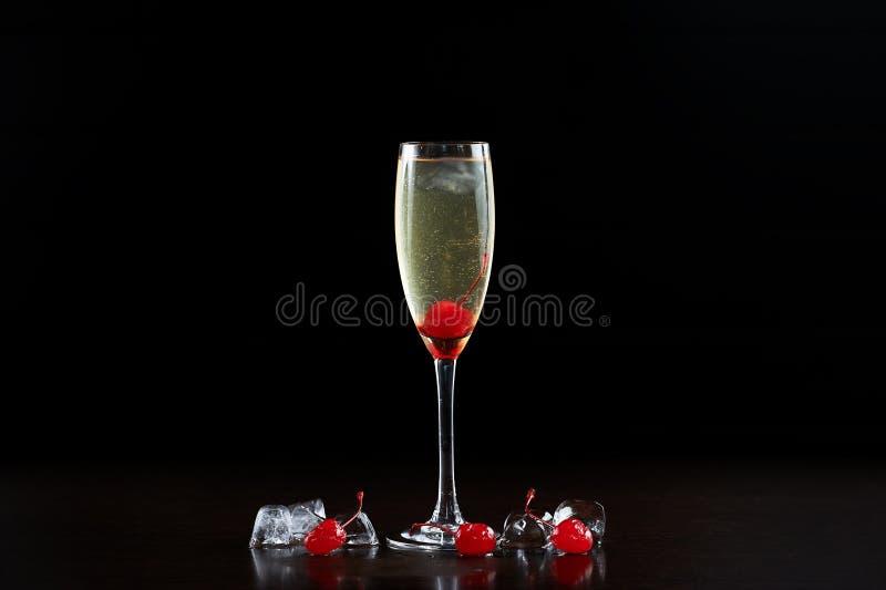 Koktajlu szkło z zimnym szampanem, dojrzałymi czerwonymi wiśniami i kostkami lodu odizolowywającym na czarnym tle, obrazy royalty free