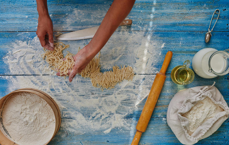 Kokvrouw die Italiaanse deegwaren voorbereiden stock afbeeldingen