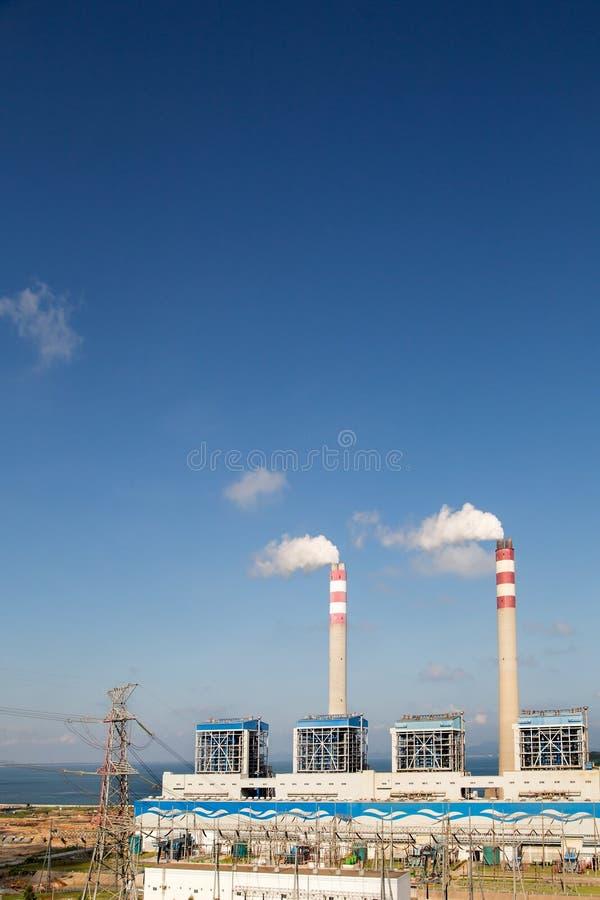 Kol-avfyrade kraftverk i bakgrunden av viten för blå himmel fördunklar arkivfoton