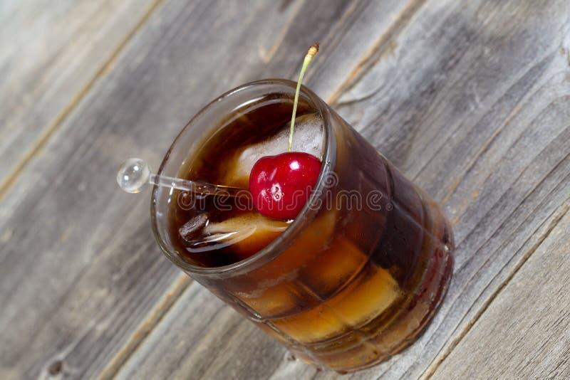 Kola en Rum met rijpe kers en ijs in Glas royalty-vrije stock afbeelding