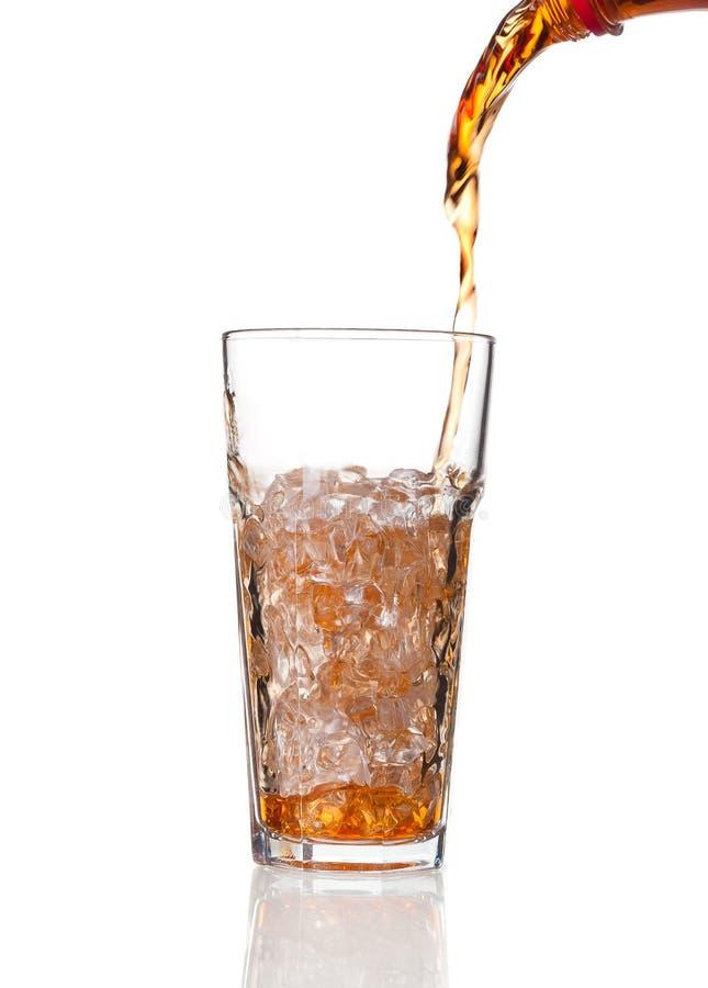 Kola se renversant dans un verre, d'isolement sur le fond blanc photo stock