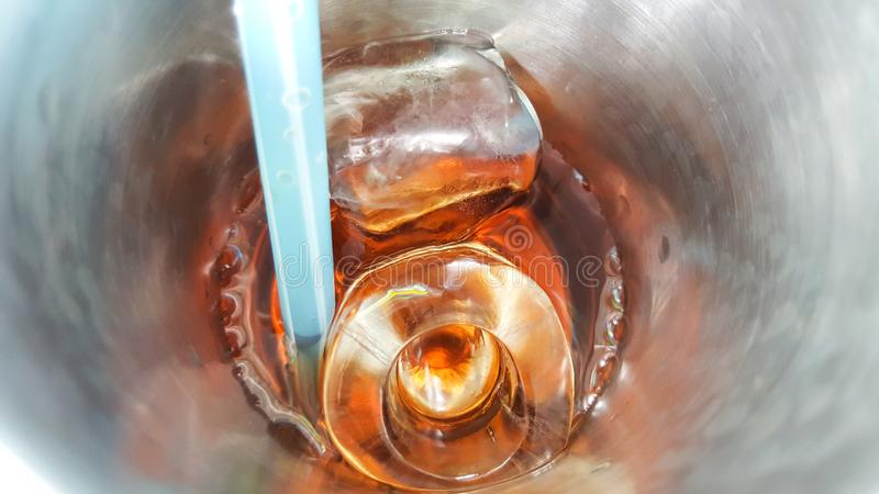 Kola z kostką lodu w stal nierdzewna kubka tle obrazy stock