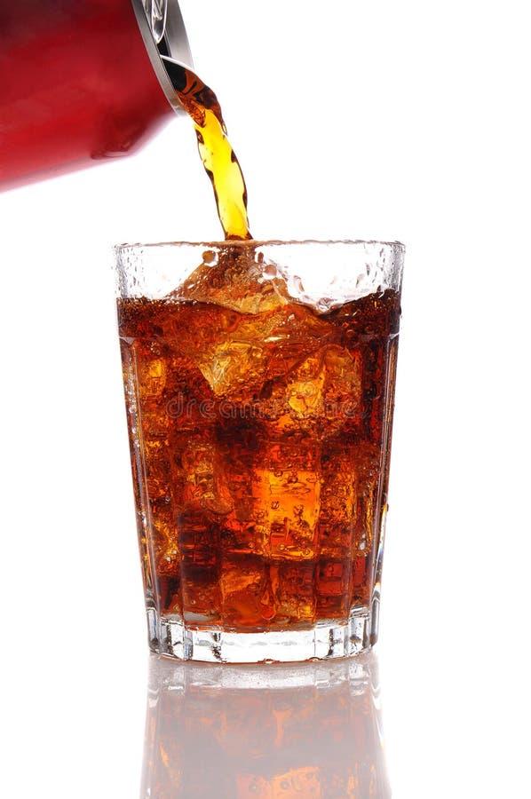 Kolabaum, der aus einer Dose in ein Glas ausläuft. stockfotos