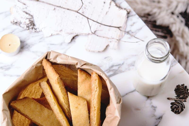 Kolakakor - Zweedse koekjes, fles van melk en kaars en denneappel op grijze marmeren lijst stock afbeeldingen