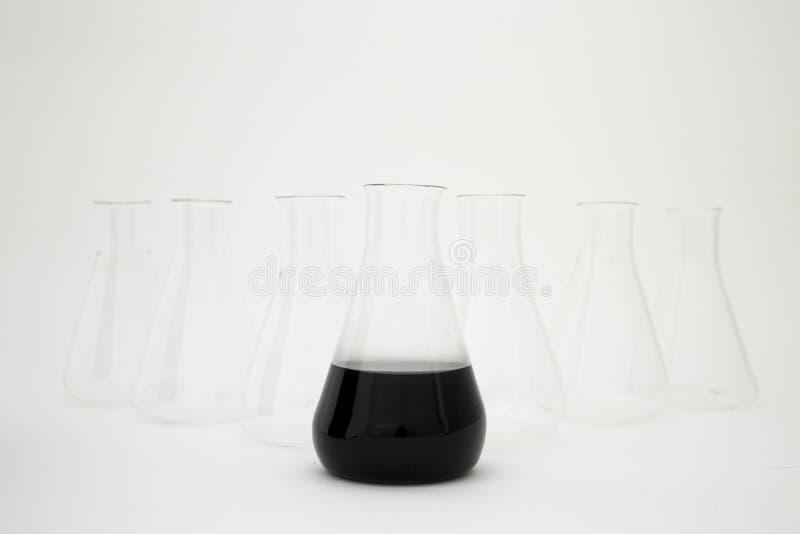 Kolba szklana szklana, szklana, wypełniona czarnym płynem z wyposażeniem szklanym na białym tle zdjęcie royalty free