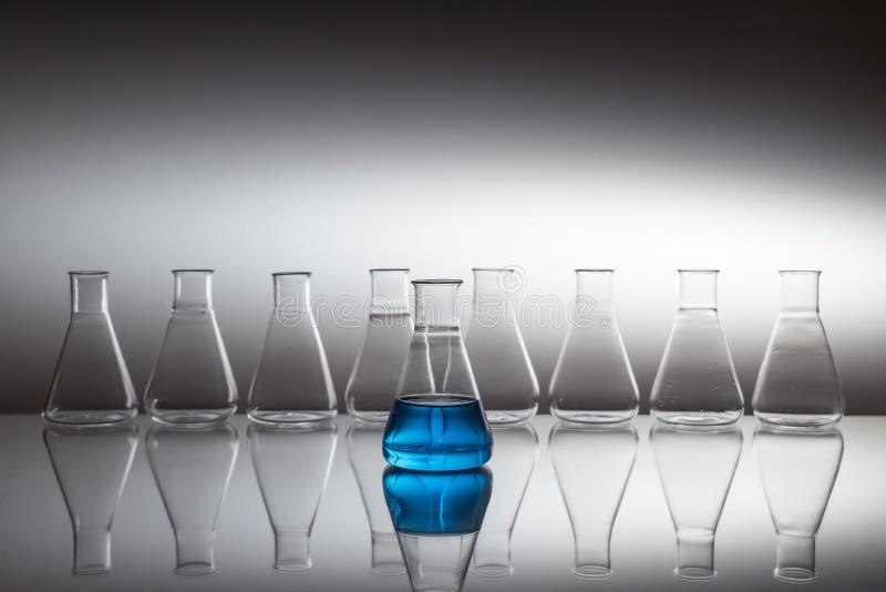 Kolba szklana szklana szklana, wypełniona niebieskim płynem z wyposażeniem szklanym na powierzchni odblaskowej zdjęcie stock