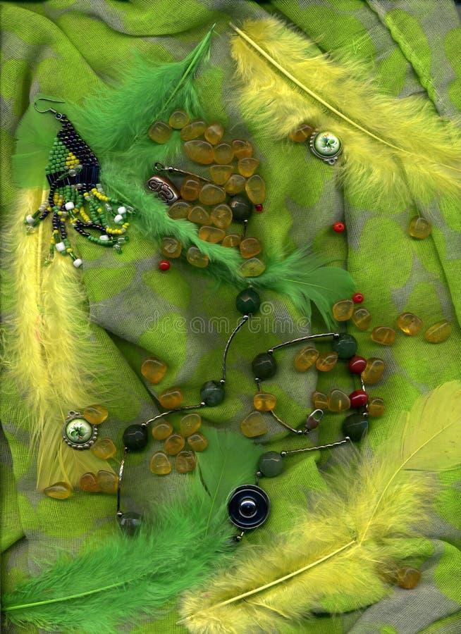 Kolczyki i piórka z złocistym lying on the beach na zielonym tekstylnym tle zdjęcia stock