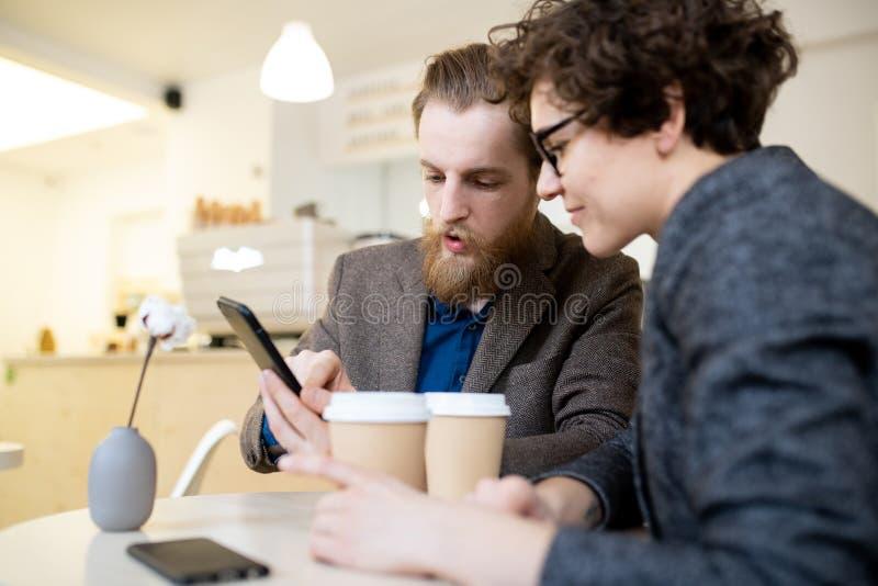 Koledzy analizuje informację na smartphone w kawiarni obrazy stock