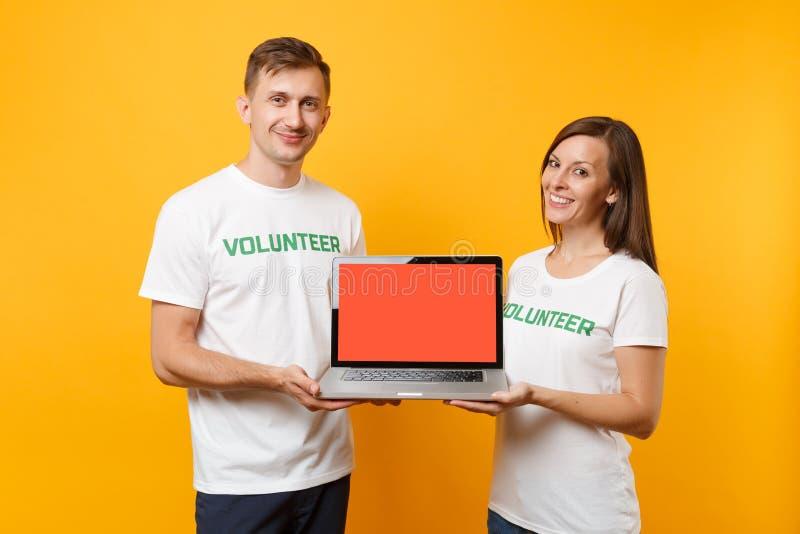 Koledzy dobierają się w białym koszulki inskrypcji wolontariusza chwyta laptopu komputeru osobistego komputerze, puste miejsce pu obrazy royalty free