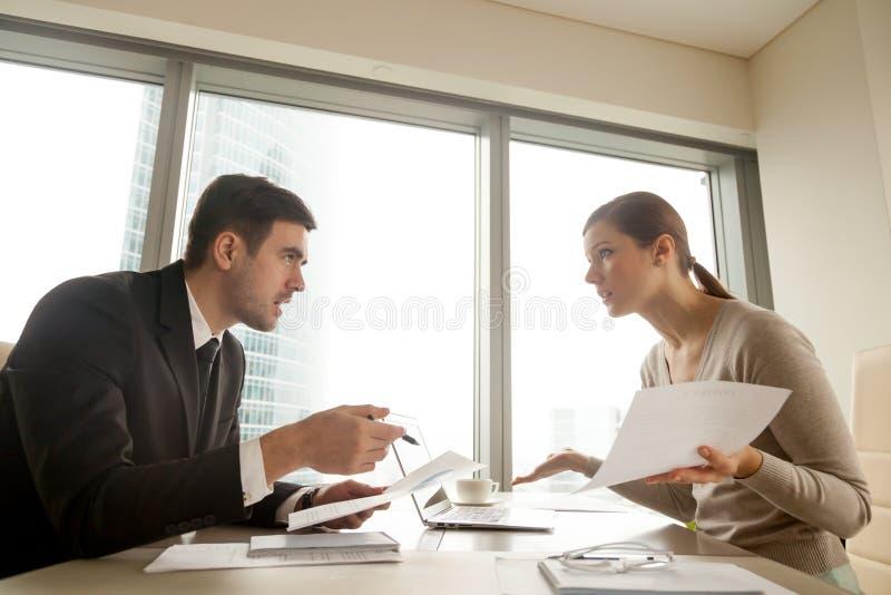 Koledzy dyskutuje przy miejscem pracy, nie zgadzać się o dokumencie, błąd obraz stock