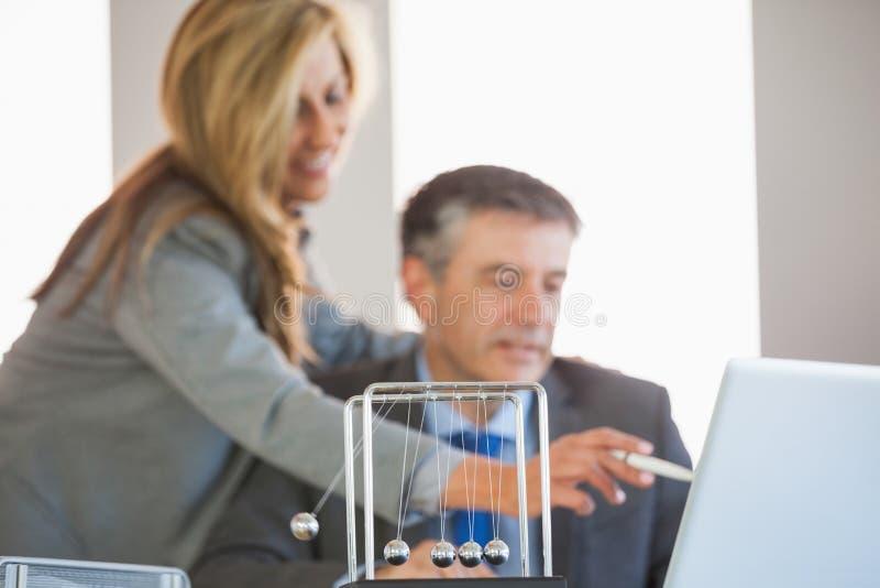 Koledzy dyskutuje w biurze z newtonami kołysankowymi w obrazy stock