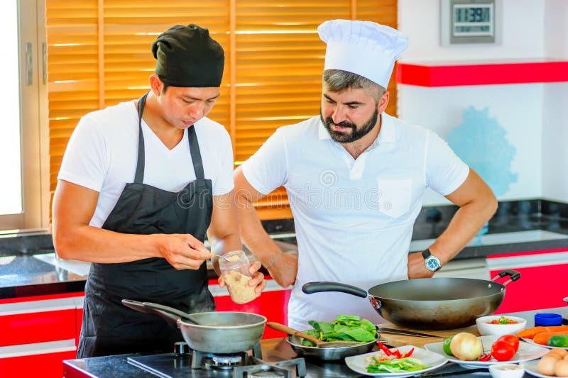 Koledzy przy pracą: Tajlandzcy i Europejscy szefowie kuchni przy kuchenny robić zdjęcie stock