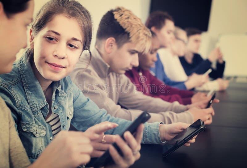 Kolega z klasy używa ich smartphones ciężko podczas klas zdjęcia royalty free