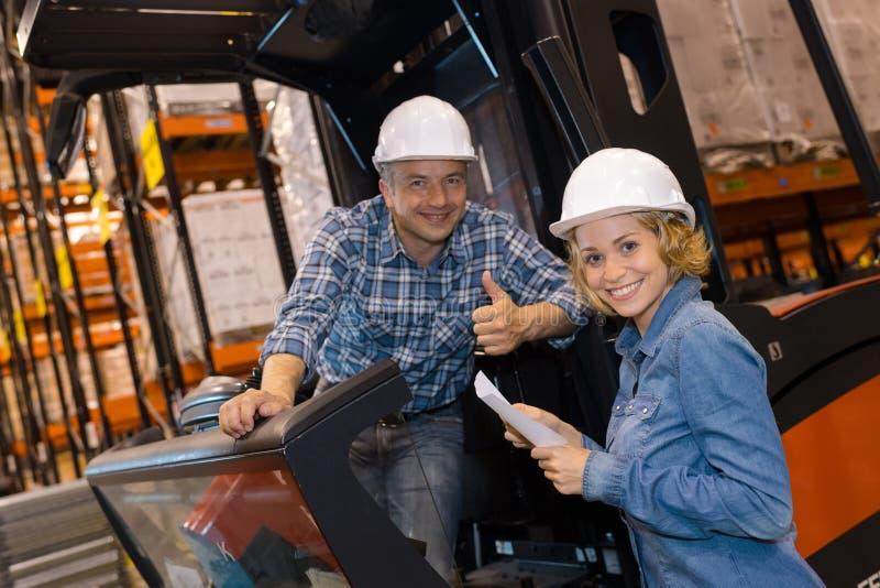 Kolegi i forklift kierowca przewozi samochodem z skończonymi towarami zdjęcia stock