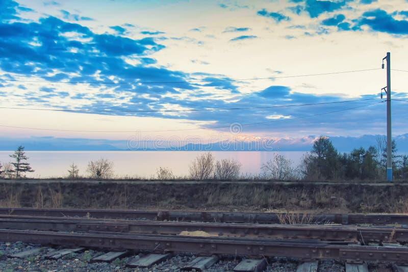 Kolej na jeziornym brzeg przy zmierzchem zdjęcie royalty free