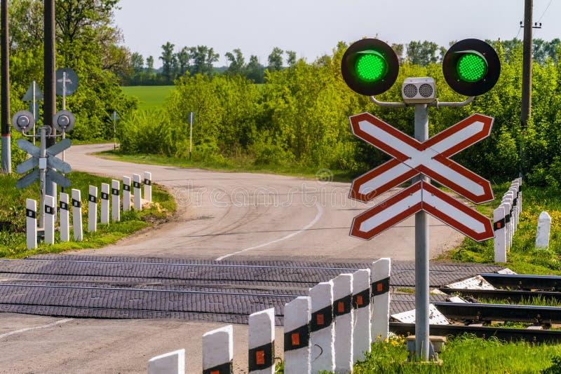 Kolejowi światła ruchu z zielonym sygnałem Kolejowy i drogowy skrzyżowanie zdjęcia royalty free