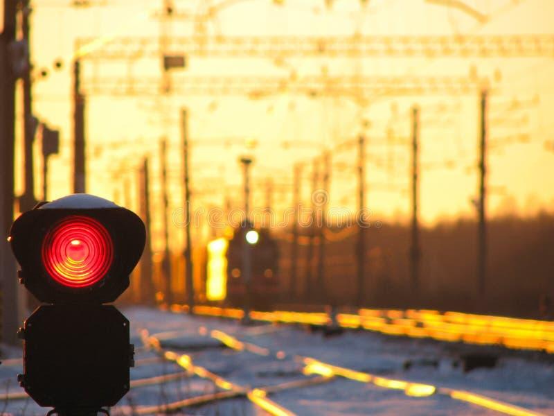 Kolejowy światła ruchu pokazuje błękita sygnał na kolei i kolej z pociągiem towarowym jako tło obraz stock