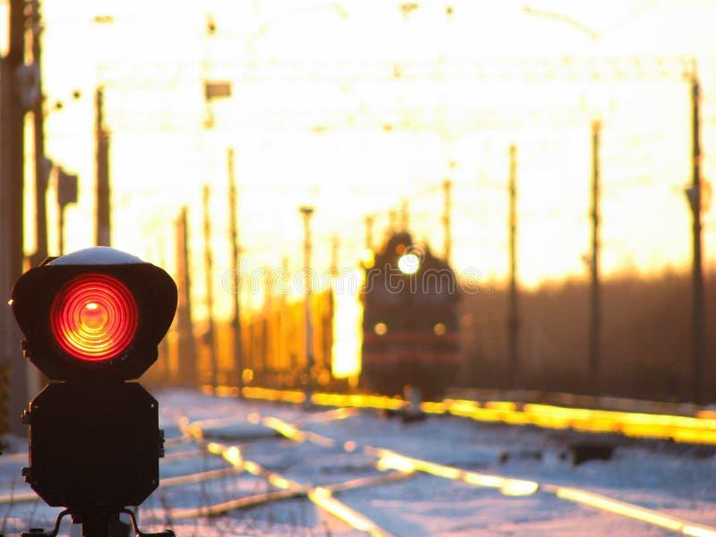 Kolejowy światła ruchu pokazuje błękita sygnał na kolei i kolej z pociągiem towarowym jako tło zdjęcie stock