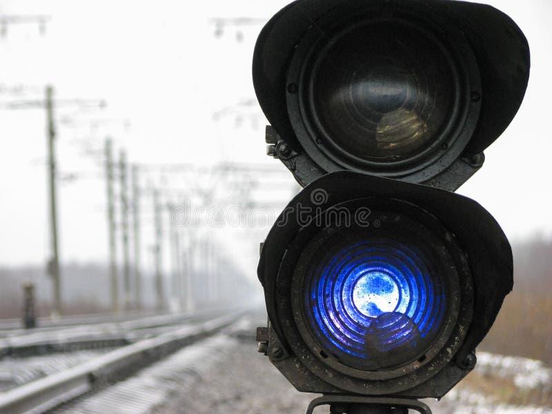 Kolejowy światła ruchu pokazuje błękita sygnał na kolei na chmurnym dniu fotografia stock