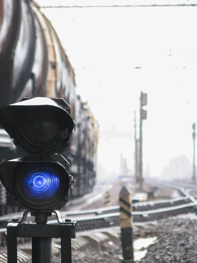 Kolejowy świateł ruchu przedstawień błękita sygnał na kolei z plama skutkiem i kolei z pociągiem towarowym jako tło fotografia royalty free