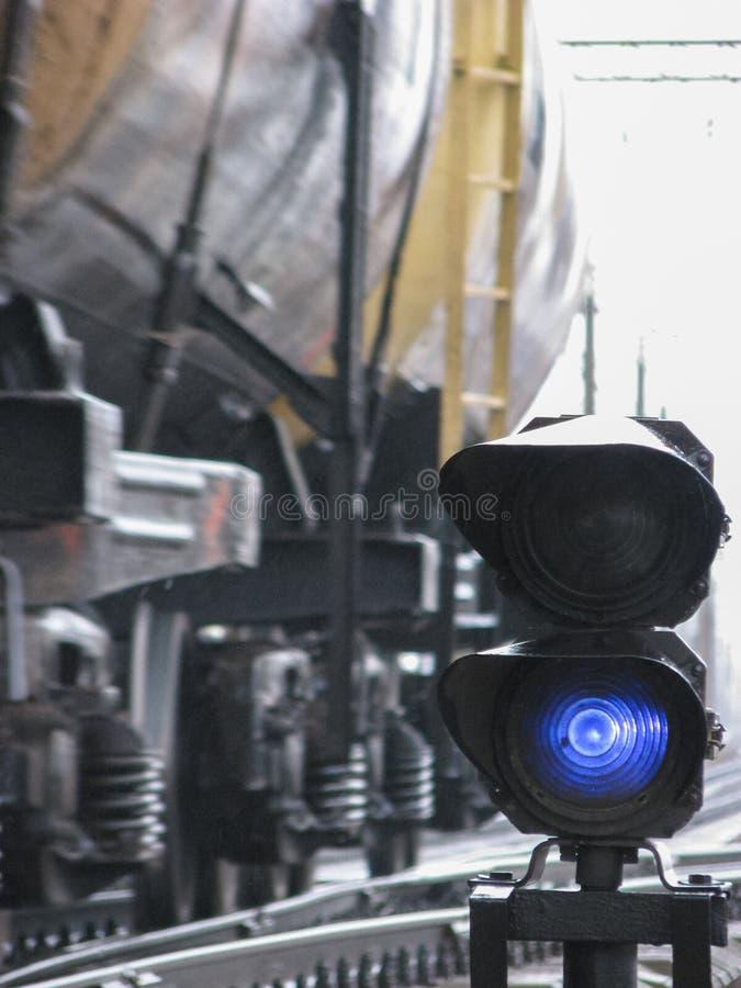 Kolejowy świateł ruchu przedstawień błękita sygnał na kolei z plama skutkiem i kolei z pociągiem towarowym jako tło zdjęcia royalty free