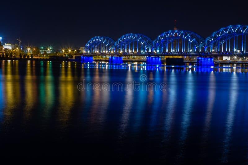Kolejowy most krzyżuje Daugava rzekę w Ryskim przy nocą Panoramiczny widok na Ryskim kapitał Latvia miasto od lewego banka obrazy royalty free
