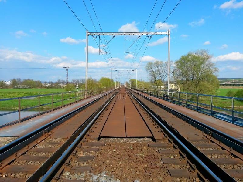 Kolejowy most nad rzeką z dwa parami ślada iść w odległość tło jest błękitnym chmurnym niebem zdjęcia stock