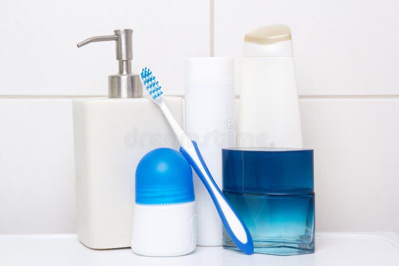 Kolekcja białe i błękitne kosmetyk butelki nad kafelkową ścianą wewnątrz zdjęcie royalty free
