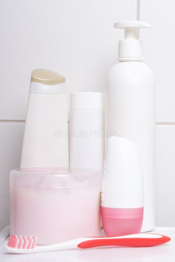 Kolekcja białe kosmetyk butelki nad kafelkową ścianą w skąpaniu fotografia stock