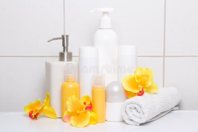 Kolekcja kosmetyk butelki z pomarańcze kwitnie nad białym ti zdjęcia stock