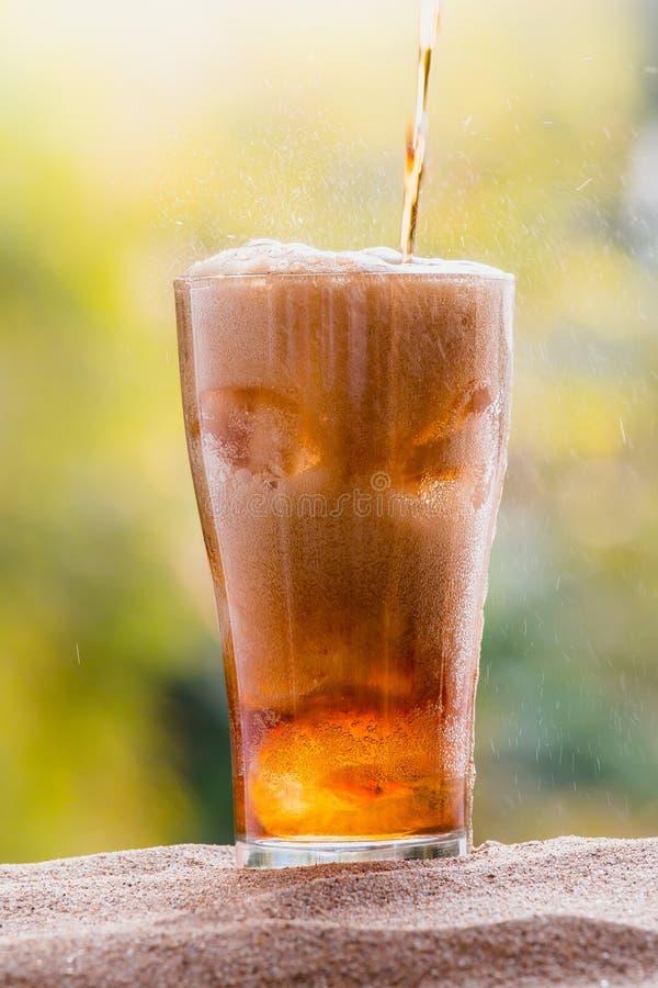 Koli wodny dolewanie w szkło z kostkami lodu na piasku obrazy royalty free