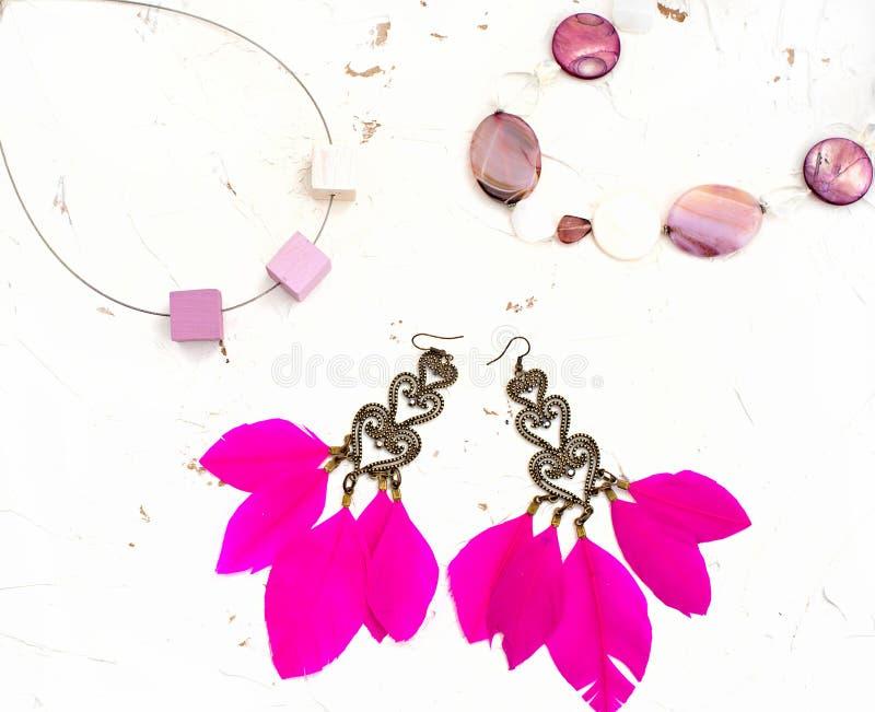 Kolia dla kobieta kolczyków z piórkami różowi białego tło zdjęcie stock