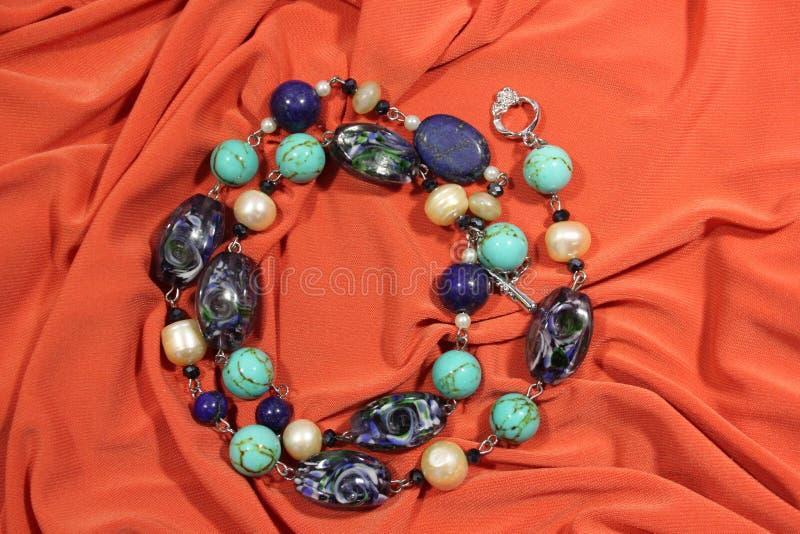 Kolia robić naturalni semiprecious kamienie - lapisu lazuli, turkus i biała rzeka, operlamy na różowym tle obraz stock
