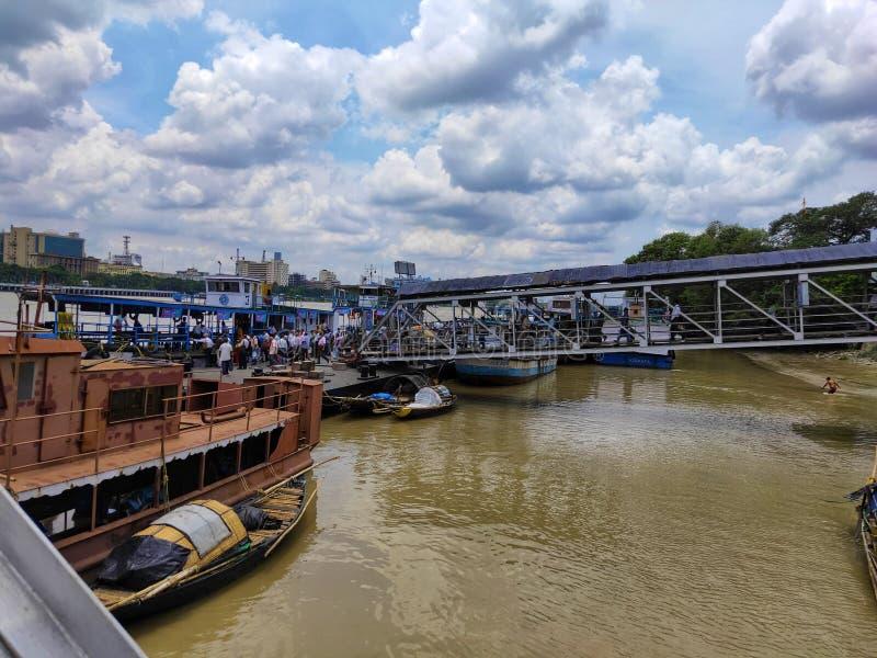 KOLKATA, ÍNDIA - 24 DE JULHO DE 2019: Os povos andam em um cais para travar o barco do transporte público no rio Hoogly Transport fotos de stock royalty free