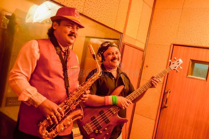 Kolkata Índia maio de 2019: Faixa do músico adulto do PNF dois e da rocha com guitarra elétrica e saxofone que ensaia em uma grav imagem de stock