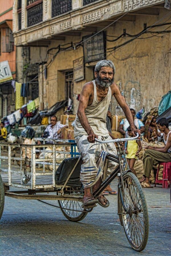 KOLKATA, ÍNDIA, outubro de 2014, Motorista de riquixá ciclista em estrada imagem de stock royalty free