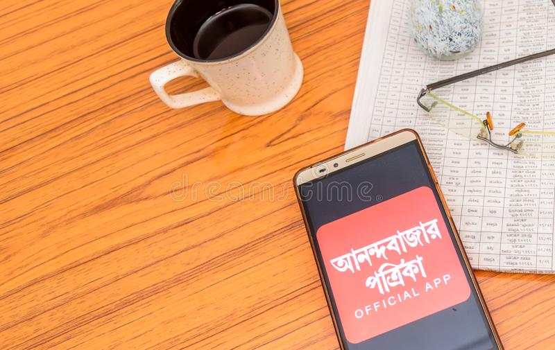 Kolkata, India, February 3, 2019: Anandabazar Patrika Bengali news app visible on mobile phone screen and placed over a wooden royalty free stock image