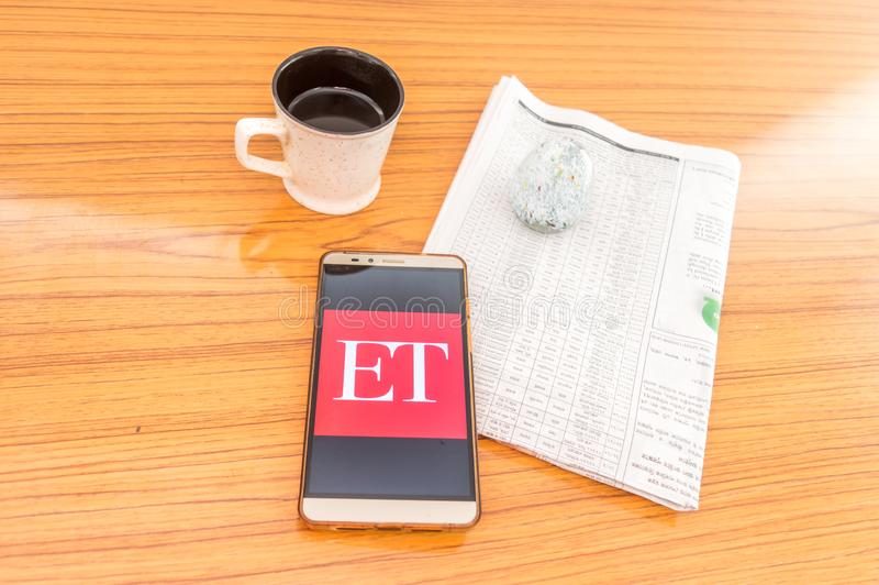 Kolkata, India, February 3, 2019: Economic Times ET news app visible on mobile phone screen beautifully placed over a wooden. Table with a newspaper and a cup royalty free stock images