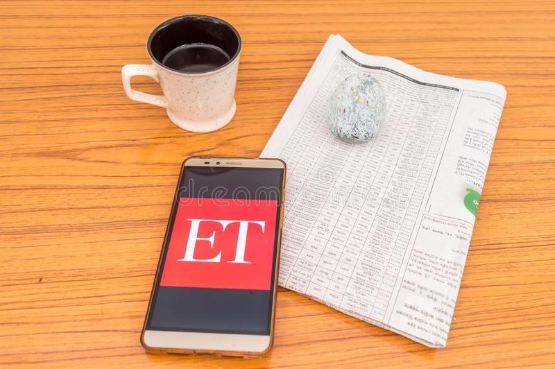 Kolkata, India, February 3, 2019: Economic Times ET news app visible on mobile phone screen beautifully placed over a wooden. Table with a newspaper and a cup royalty free stock photography