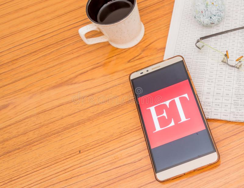 Kolkata, India, February 3, 2019: Economic Times ET news app visible on mobile phone screen beautifully placed over a wooden. Table with a newspaper and a cup stock image